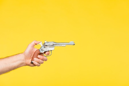 cropped shot of person holding revolver isolated on yellow