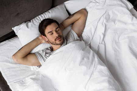 top view of handsome bearded young man sleeping with hands behind head in bed 写真素材