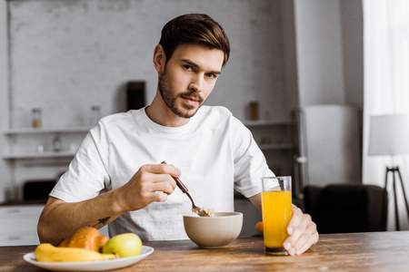 handsome young man having cereal with orange juice and looking at camera at home
