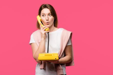 surprised young woman talking by rotary phone isolated on pink Stock Photo