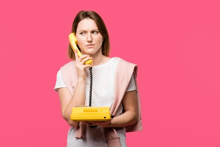 young woman with frowning eyebrows talking by handset isolated on pink