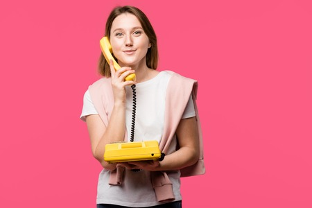 beautiful young woman talking by rotary phone and smiling at camera isolated on pink Stock Photo