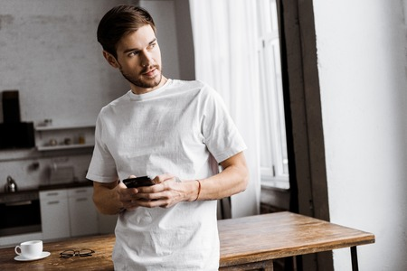 handsome young man using smartphone and looking away at home