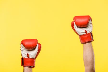 abgeschnittene Aufnahme einer Person in Boxhandschuhen isoliert auf Gelb