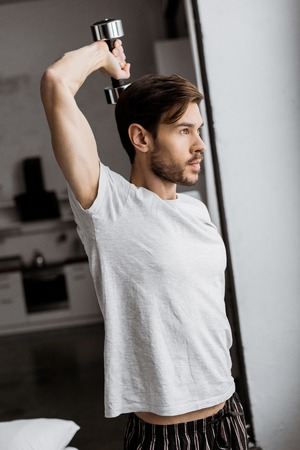 handsome young man in pajamas exercising with dumbbell and looking away in the morning Stok Fotoğraf