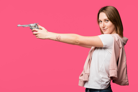 side view of young woman holding revolver and smiling at camera isolated on pink