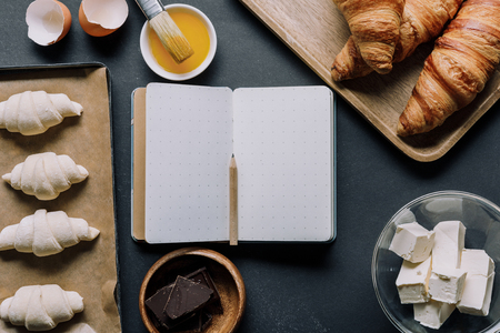 flat lay with blank textbook surrounded by dough for croissants and ingredients on table