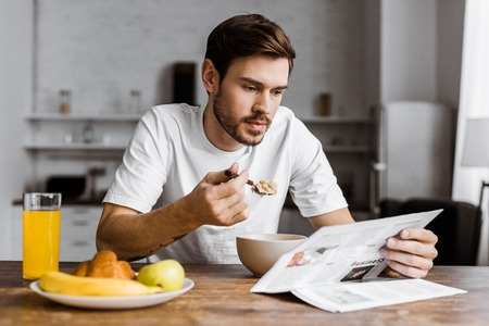 handsome young man having cereal for breakfast and reading newspaper at home Stock Photo