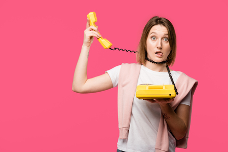young woman with wire around neck holding rotary phone and looking at camera isolated on pink Stock Photo