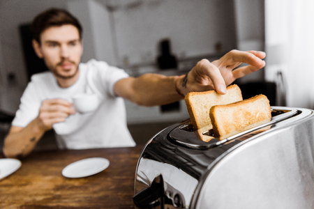 close-up shot of young man drinking coffee and taking toast from toaster Archivio Fotografico