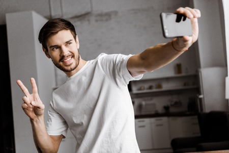 handsome young man taking selfie and making peace gesture at home 版權商用圖片 - 112608757