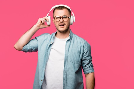 dissatisfied young man in eyeglasses wearing headphones and looking at camera isolated on pink