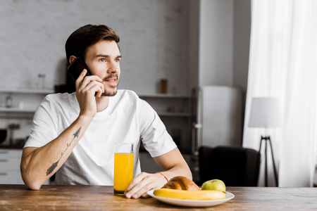 handsome young man talking by smartphone during with glass of orange juice and fruits on table at home