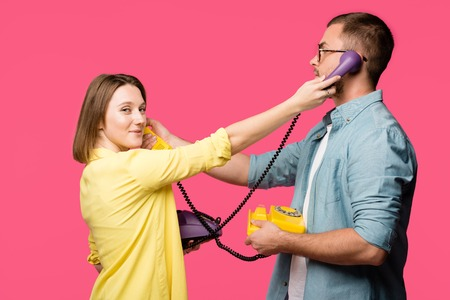 young man and woman holding rotary phones and handsets for each other isolated on pink Stock Photo