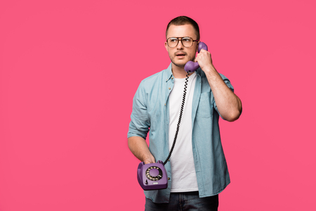 serious young man in eyeglasses talking by vintage telephone isolated on pink