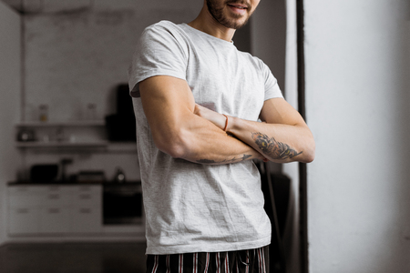 cropped shot of handsome young man with crossed arms in pajamas standing at home 版權商用圖片