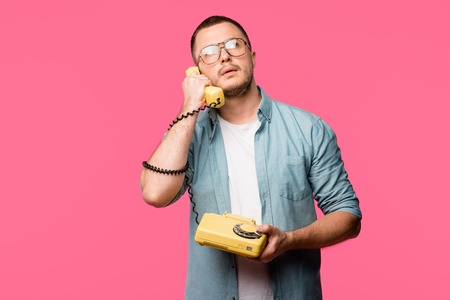 young man in eyeglasses talking by rotary phone and looking up isolated on pink