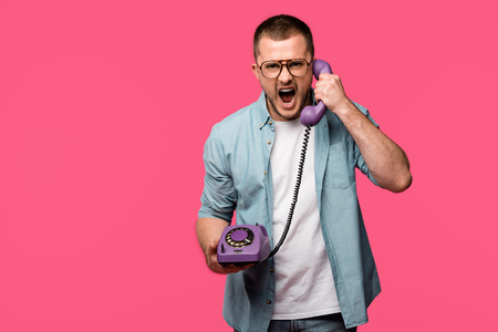 emotional young man yelling at handset and looking at camera isolated on pink