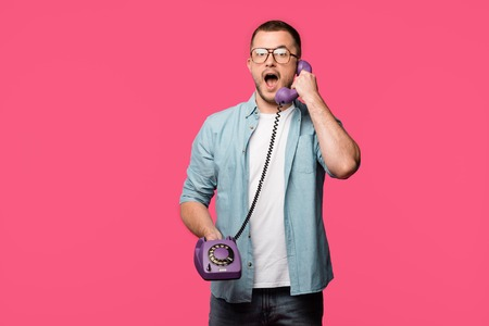 shocked man in eyeglasses talking by vintage telephone and looking at camera isolated on pink