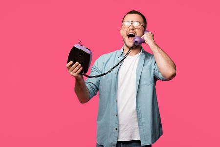 excited young man in eyeglasses talking by vintage telephone isolated on pink Stock Photo