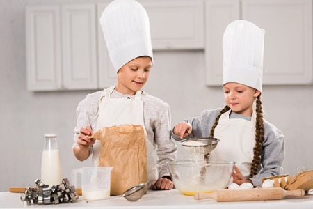 happy kids in aprons sifting flour through sieve into bowl at table in kitchen