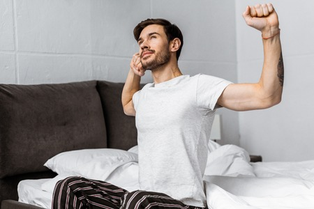 handsome bearded young man in pajamas stretching while sitting in bed