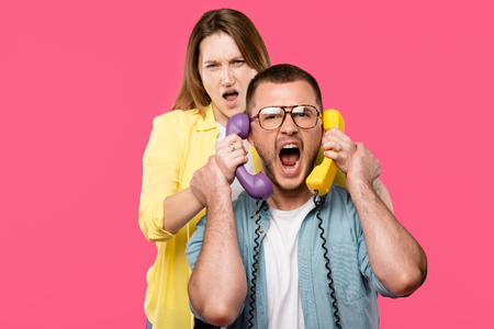 young woman holding handsets and man in eyeglasses yelling isolated on pink