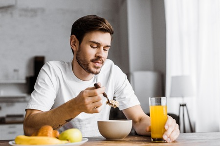handsome young man having cereal with orange juice at home