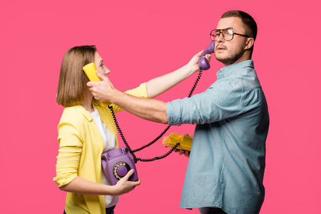 side view of young man and woman holding rotary phones and handsets for each other isolated on pink