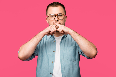 young man in eyeglasses gesturing for silence and holding crossed fingers near lips isolated on pink Banco de Imagens