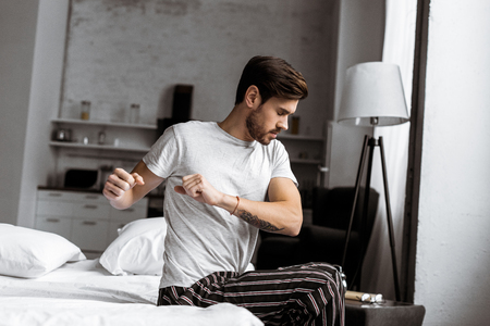 young man in pajamas exercising and stretching while sitting in bed in the morning