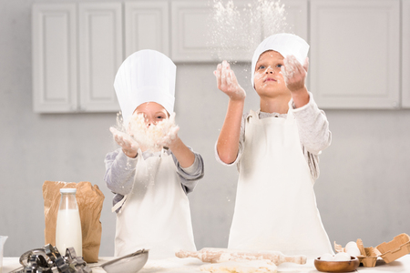 sister and brother in chef hats having fun with flour in kitchen