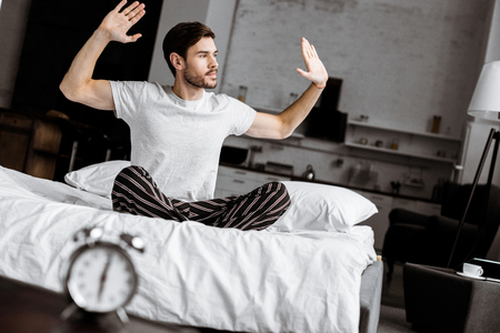 handsome young man in pajamas sitting on bed and raising hands in the morning Stok Fotoğraf