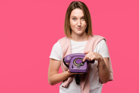 beautiful young woman holding rotary phone and smiling at camera isolated on pink