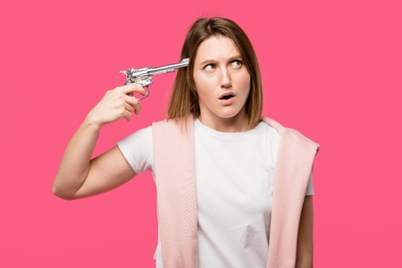 young woman holding revolver near head and looking away isolated on pink