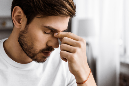 close-up portrait of depressed young man touching nose bridge at home