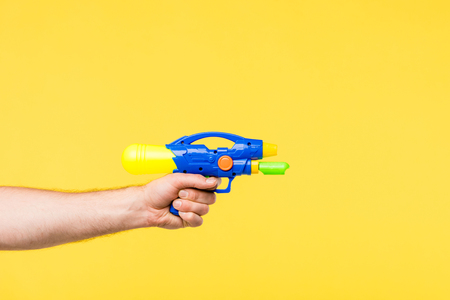 cropped shot of person holding toy gun isolated on yellow