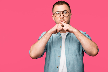shocked young man gesturing for silence and holding crossed fingers near lips isolated on pink