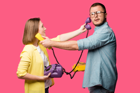 side view of young couple holding rotary phones and handsets for each other isolated on pink Stock Photo