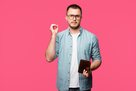 young man holding empty wallet and showing zero sign isolated on pink