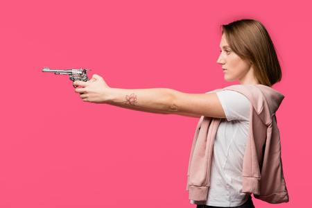 side view of young woman holding revolver and looking away isolated on pink Фото со стока