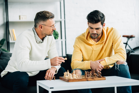 son and mature father playing chess together on weekend in living room