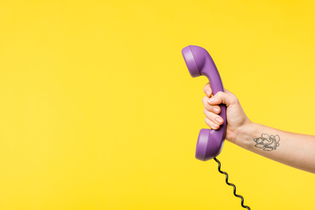 cropped shot of person holding purple handset isolated on yellow