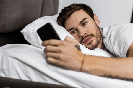 handsome bearded young man lying in bed and using smartphone 版權商用圖片 - 112610233