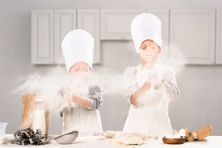 selective focus of brother and sister in chef hats having fun with flour in kitchen Stock Photo - 112610237