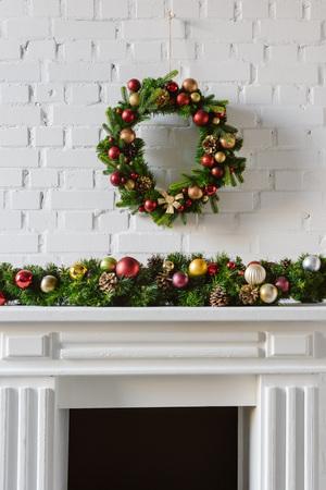 festlicher Weihnachtskranz über Kaminsims mit weißer Backsteinmauer