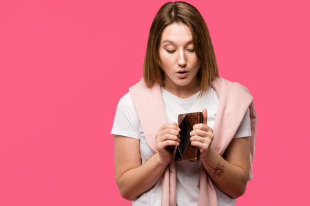 shocked young woman looking into empty wallet isolated on pink