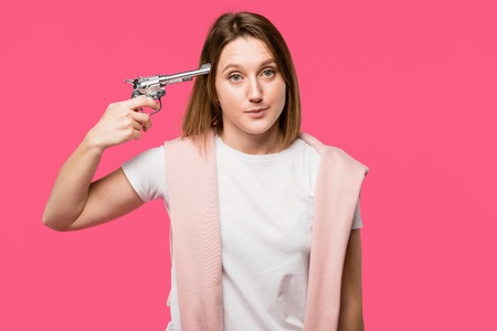 young woman holding revolver near head and looking at camera isolated on pink Zdjęcie Seryjne
