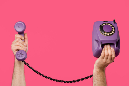 cropped shot of man holding purple rotary phone isolated on pink Banco de Imagens