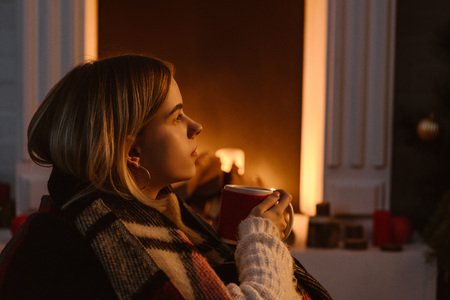 side view of young woman in checkered blanket holding mug of cocoa at home 스톡 콘텐츠 - 112610673